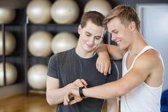 Amis masculins vérifiant le podomètre dans le gymnase Photo libre de droits