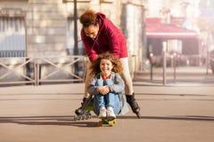 Amis mignons avec la planche à roulettes et les patins ayant l'amusement Photos libres de droits