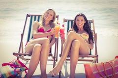 Amis mignons ayant des cocktails sur la plage Images stock