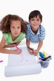 Amis mignons dessinant tout en se trouvant sur l'étage Photos stock