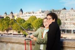 Amis mignons prenant la photo utilisant un bâton de selfie Photos stock