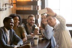 Amis millénaires ayant l'amusement faisant le selfie en café Photos libres de droits