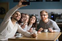 Amis millénaires divers prenant le selfie de groupe sur le téléphone portable dans c Photos stock