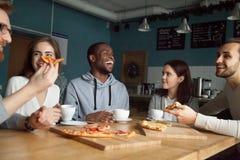 Amis millénaires heureux multiraciaux riant mangeant le toget de pizza Images libres de droits