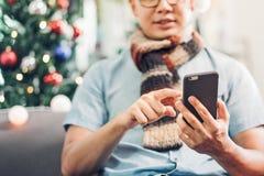 Amis mobiles d'appel d'utilisation de chapeau de Santa d'usage d'homme de l'Asie et se reposer sur s Photos stock