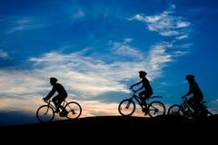 Amis montant des bicyclettes au ciel de coucher du soleil Photographie stock libre de droits
