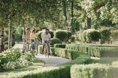 Amis montant des bicyclettes en parc Image stock