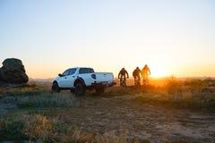 Amis montant des vélos dans les montagnes devant le camion d'Off Road de collecte au coucher du soleil Concept d'aventure et de v photo libre de droits