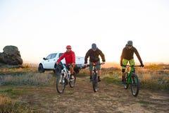 Amis montant des vélos dans les montagnes devant le camion d'Off Road de collecte au coucher du soleil Concept d'aventure et de v photographie stock libre de droits