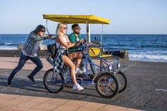 Amis montant sur le chariot de bicyclette au bord de la mer Image libre de droits