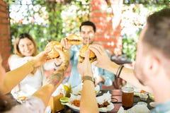 Amis montrant l'excitation en grillant des hamburgers photographie stock libre de droits