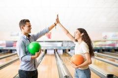 Amis montrant Teamspirit avec un top-là au bowling Photographie stock libre de droits
