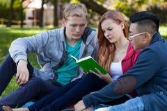 Amis multi-ethniques étudiant à l'examen Photo stock