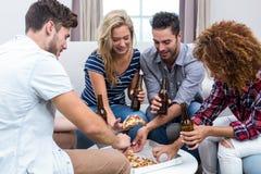Amis multi-ethniques appréciant la bière et la pizza Photographie stock