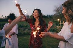 Amis multi-ethniques appréciant la partie avec des cierges magiques Images stock