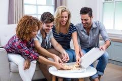 Amis multi-ethniques appréciant la pizza à la maison Photo stock