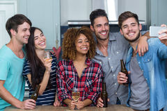 Amis multi-ethniques avec de l'alcool prenant le selfie dans la cuisine Image libre de droits