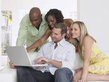 Amis multi-ethniques avec l'ordinateur portable Photos stock