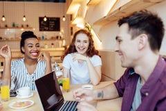 Amis multi-ethniques avec l'ordinateur portable en café Images stock