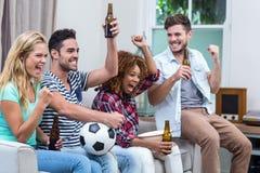 Amis multi-ethniques avec la bouteille à bière appréciant le match de football Images stock