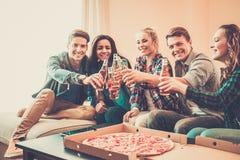 Amis multi-ethniques avec la pizza et les bouteilles de boissons Image stock