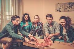 Amis multi-ethniques avec la pizza et les bouteilles de la boisson Image libre de droits