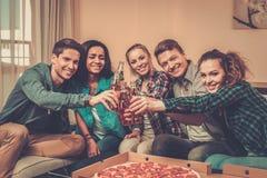 Amis multi-ethniques avec la pizza et les bouteilles de la boisson Photographie stock libre de droits