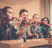 Amis multi-ethniques avec la pizza et les bouteilles de la boisson Image stock