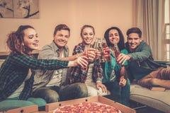 Amis multi-ethniques avec la pizza et les bouteilles de la boisson Photos stock