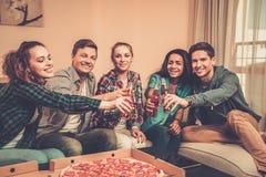 Amis multi-ethniques avec la pizza et les bouteilles de la boisson Images stock