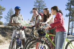 Amis multi-ethniques avec les vélos et la carte Photo stock
