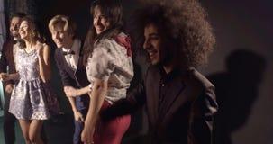 Amis multi-ethniques ayant l'amusement, dansant clips vidéos