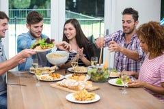 Amis multi-ethniques ayant le repas à la table dans la maison Photo stock