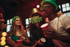 Amis multi-ethniques célébrant le jour du ` s de St Patrick dans la boîte de nuit Images libres de droits