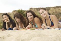 Amis multi-ethniques détendant à la plage Image libre de droits