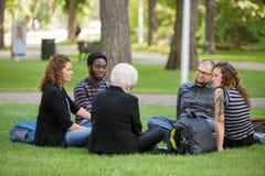 Amis multi-ethniques détendant sur l'herbe au campus Photos libres de droits