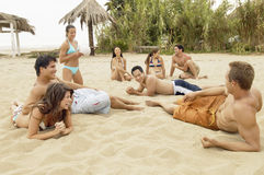 Amis multi-ethniques détendant sur la plage Image stock
