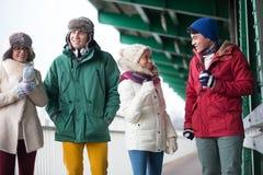 Amis multi-ethniques dans l'usage d'hiver conversant dehors Photo stock