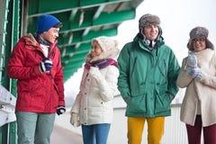 Amis multi-ethniques dans l'usage d'hiver conversant dehors Image stock