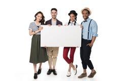 Amis multi-ethniques de sourire de jeunes tenant la bannière vide Image stock
