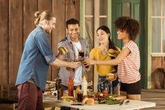Amis multi-ethniques de sourire faisant tinter avec des verres de kola au pique-nique sur le patio Images libres de droits