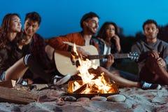 Amis multi-ethniques de sourire passant le temps près du feu de camp Image libre de droits