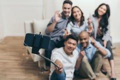Amis multi-ethniques de sourire prenant le selfie avec le monopod et le smartphone à la maison Image stock