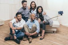 Amis multi-ethniques de sourire prenant le selfie avec le monopod et le smartphone à la maison Images stock