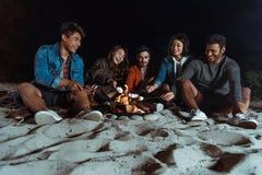 Amis multi-ethniques de sourire rôtissant des guimauves sur le feu à la plage sablonneuse Photos libres de droits