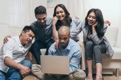 Amis multi-ethniques de sourire regardant l'ordinateur portable tout en se reposant sur le sofa à la maison Photo stock
