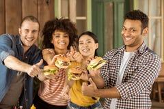 Amis multi-ethniques de sourire tenant des hamburgers au pique-nique sur le patio Photo stock
