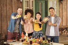 Amis multi-ethniques de sourire tenant des hamburgers et montrant des pouces au pique-nique Photographie stock libre de droits