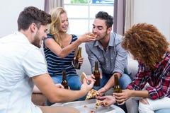 Amis multi-ethniques gais appréciant la bière et la pizza Photos stock