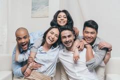 Amis multi-ethniques gais embrassant tout en se reposant sur le sofa à la maison Images stock